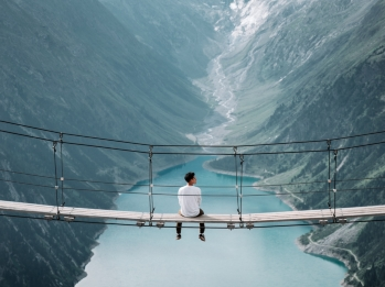 Man sitting on a footbridge spanning two mountains