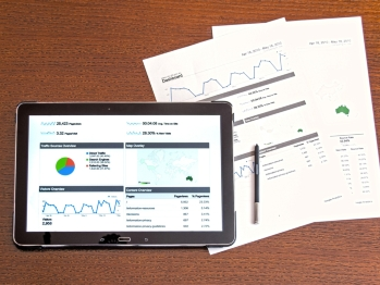 Ipad and papers showing charts and graphs