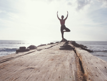 Woman standing on a pier next to the ocean in a yoga pose back lit by the sun