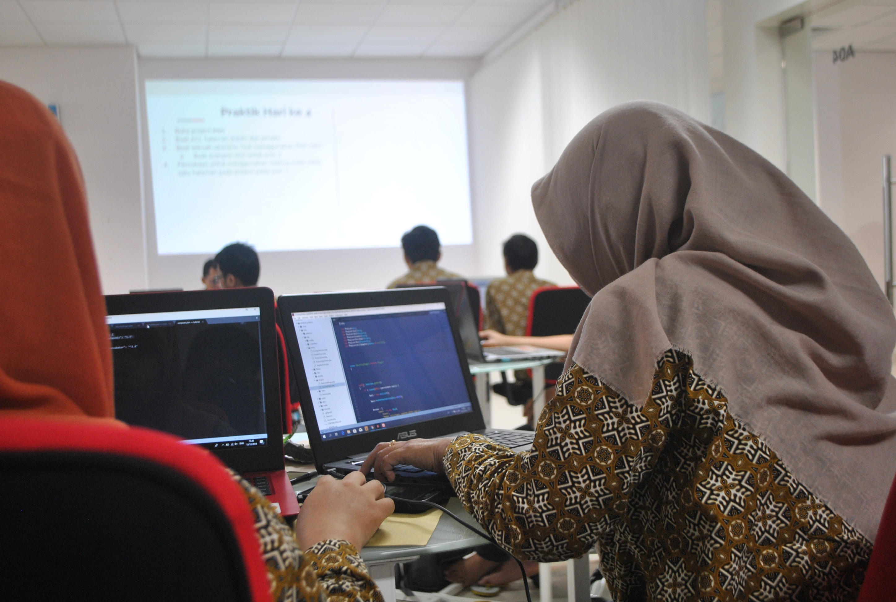 Two women in hijab at laptops in a classroom