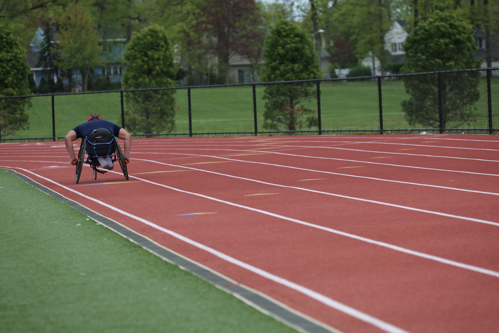 Person in wheelchair racing around track.